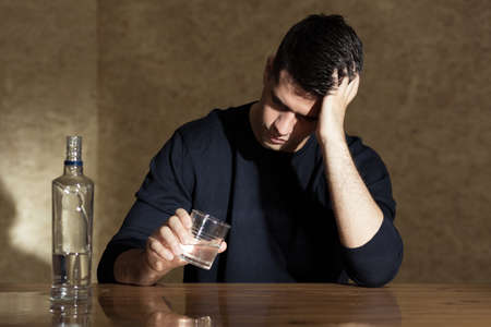 alcohol addiction: Young man drinking vodka in the glass Stock Photo