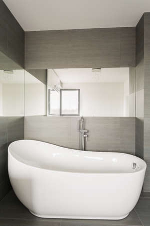 tiling: Close up of large stylish bathtub in grey tiling bathroom