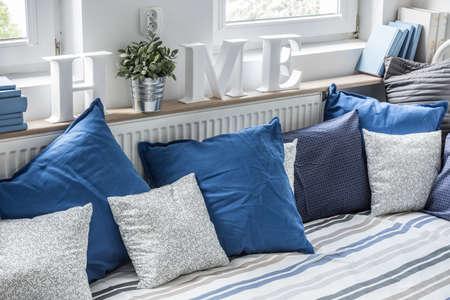 Cozy bed with lots of pillows in children bedroom Foto de archivo
