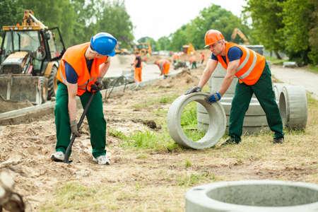 trabajando duro: Foto de dos constructores trabajando duro en un camino Foto de archivo