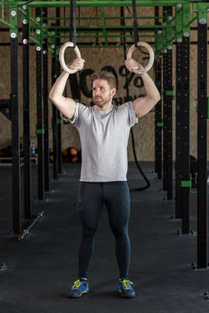 muscled: Muscled man practicing cross fit with rings Stock Photo