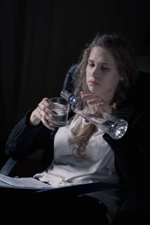 work addicted: Alcoholic woman pouring vodka into glass, vertical