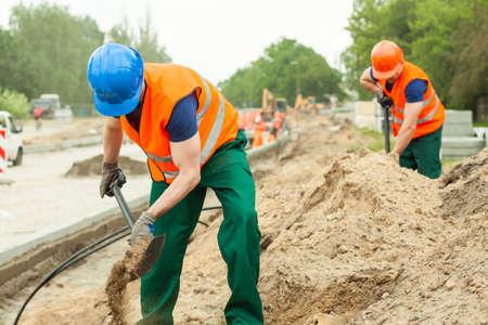 Foto de los trabajadores de la construcción de excavación en un sitio de construcción
