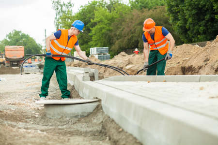 kerb: Two builders working together on a construction site