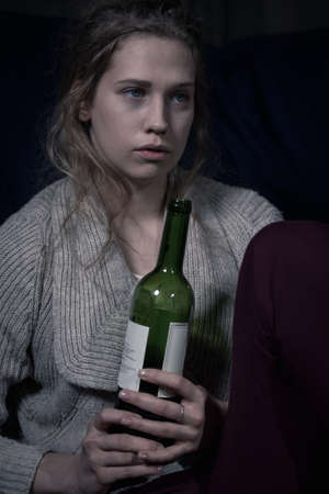 drunk girl: Young lonely woman with bottle of wine Stock Photo