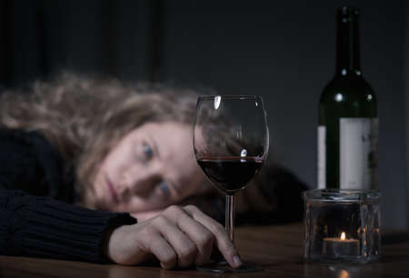 depression: Young addicted depressed woman with red wine