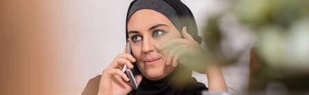 ethnic woman: Panorama of modern arabic woman in hijab talking on mobilephone