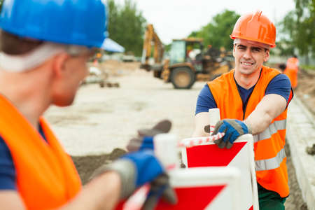 road safety: Close up of builders working along on construction site