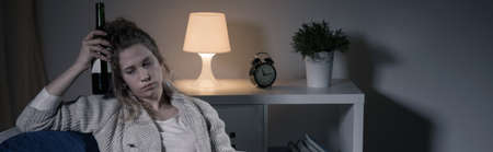 work addicted: Depressed addicted alcoholic woman drinking wine alone