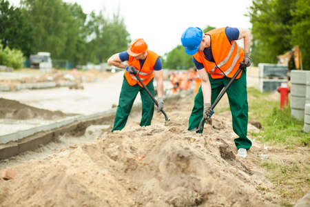 kerb: Image of construction workers digging on a road Stock Photo