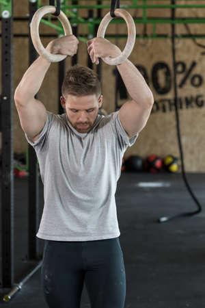 fitness hombres: hombre fuerte atractivo joven con anillos de gimnasia en el gimnasio