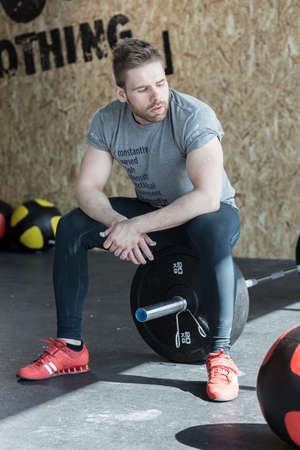 weightlifter: Weightlifter sitting on the barbell and resting after workout