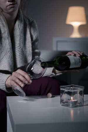 woman alone: Young sad woman pouring wine into glass