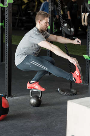 muscled: Young man practicing balancing squat on the kettlebar