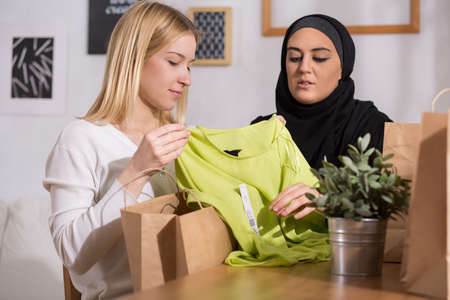 burka: Image of blonde showing new clothes to her arabic friend