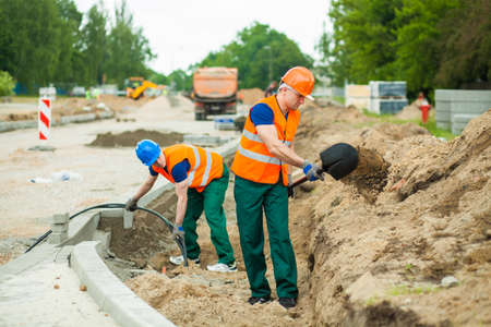 kerb: Photo of two builders standing on a construction site Stock Photo