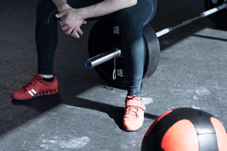 Man with gym exercise equipment - barbell and ball