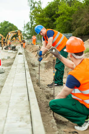construction workers: Two builders working together on a road construction Stock Photo