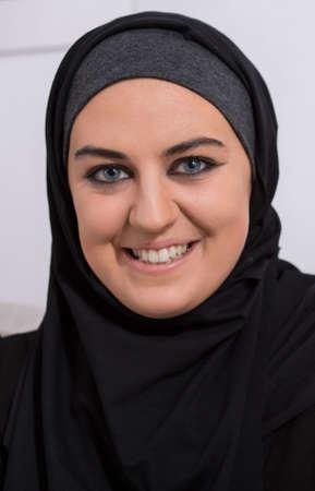 hijab: Portrait of smiling arabic woman wearing traditional black hijab