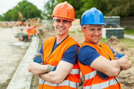 construction workers: Image of happy young builders in helmets at work