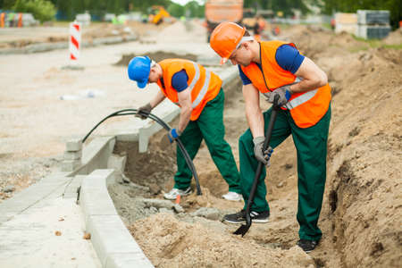 labourers: Photo of labourers working on a road construction Stock Photo