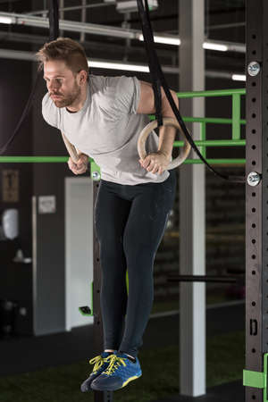 workouts: Muscled man doing crossfit exercises with gymnastic rings Stock Photo