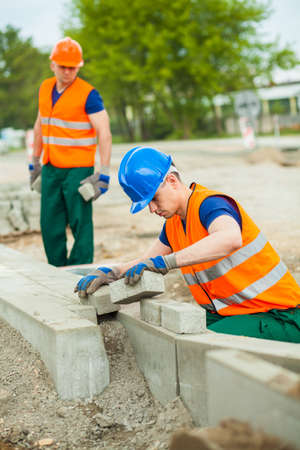 kerb: Photo of young construction worker laying cobblestones