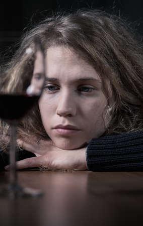 femme blonde: Sad jeune femme de boire du vin rouge seul Banque d'images