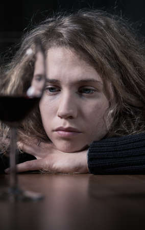 abuse young woman: Sad young woman drinking red wine alone