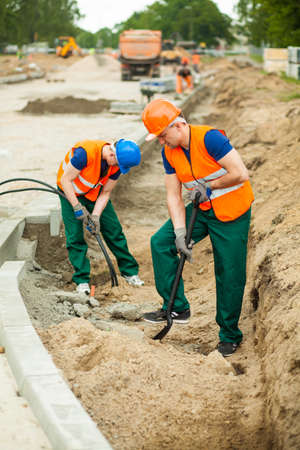 kerb: Photo of two builders working on a construction site