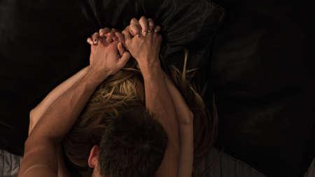 sexuales: Pareja haciendo el amor apasionado y tomados de la mano
