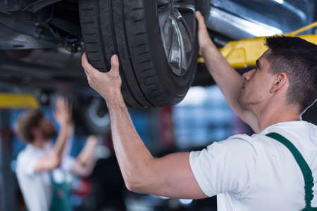 lifted: Image of car mechanic checking wheel of lifted vehicle