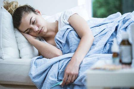 persona enferma: Mujer joven con el sueño de la gripe en la cama