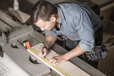 muebles de madera: carpintero ocupado usando una cinta de medir con precisión