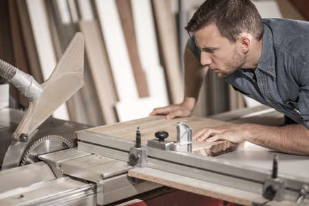 hardworking: Young worker cutting wood with sawing machine