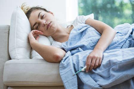 personas enfermas: Mujer febril miente bajo la manta con el term�metro Foto de archivo