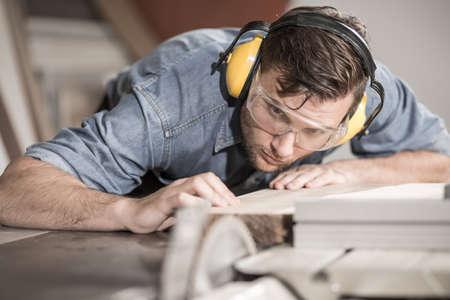 carpintero: Carpintero enfocada en el trabajo con un tablón de madera