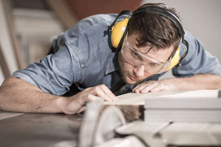 safety goggles: Focused carpenter at work with wooden plank