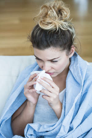 cold season: Feverish woman with tissue blowing the nose