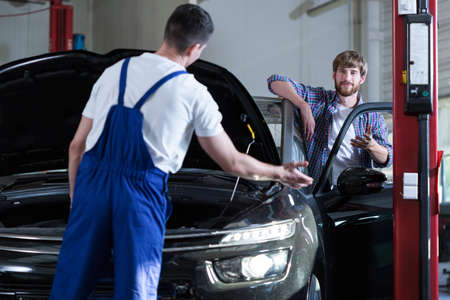 diagnosing: Image of young driver and auto service worker diagnosing car