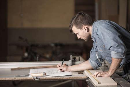 carpintero: Carpintero en el trabajo mirando cuidadosamente los planes
