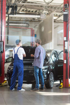 car in garage: Image of driver and auto mechanic at workshop