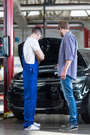 diagnosing: Picture of young car mechanic diagnosing auto of male driver
