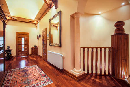gloss: Picture of spacious hallway with wooden floor and decorative rug