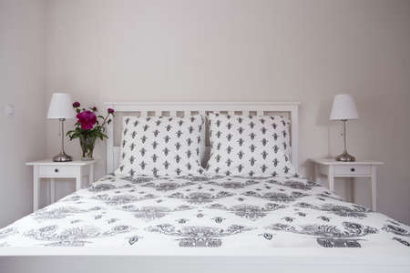 nightstands: Close up of white double bed with decorative elegant bedding Stock Photo