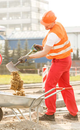 建設労働者は、手押し車に砂を注ぐ