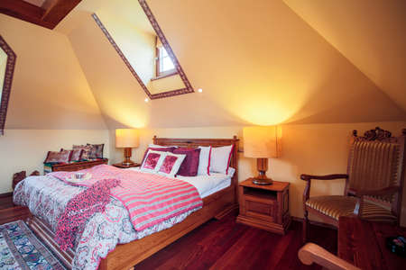 cosy: Picture of solid bed with decorative bedding in cosy room