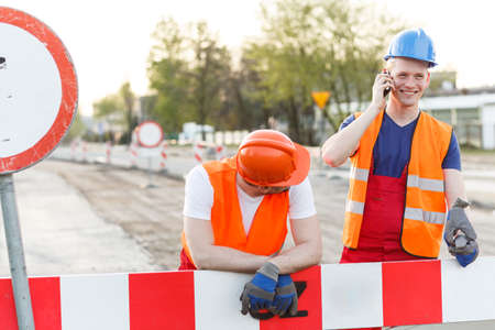 sidewalk talk: Construction workers have a break for a call Stock Photo