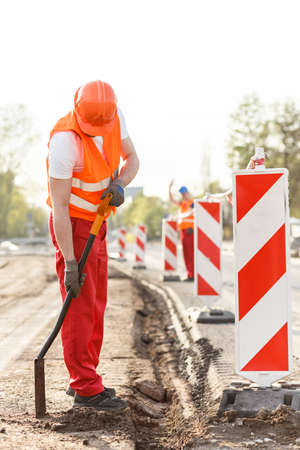 smoothing: Male construction worker is smoothing the ground Stock Photo