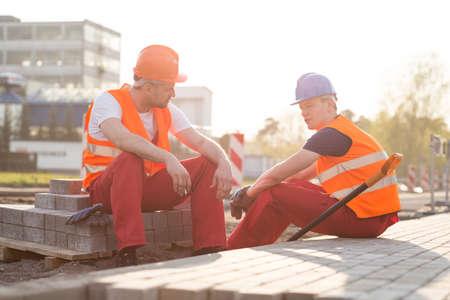 trabajadores: Trabajadores de la construcción tienen un pequeño descanso para fumar un cigarrillo